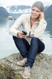 Jeune femme blond avec son Smartphone dans la main Photographie stock libre de droits