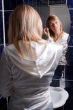 Jeune femme blond dans la salle de bains appliquant le renivellement Photos libres de droits