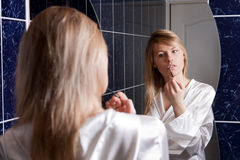 Jeune femme blond dans la salle de bains appliquant le renivellement Image stock