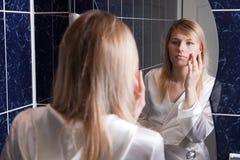 Jeune femme blond dans la salle de bains appliquant le renivellement Photographie stock libre de droits