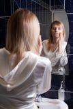 Jeune femme blond dans la salle de bains appliquant le renivellement Photo stock