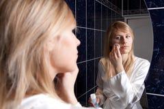 Jeune femme blond dans la salle de bains appliquant le renivellement Photos stock