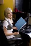 Jeune femme blond travaillant derrière le bureau image stock