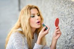 Jeune femme blonde appliquant le rouge à lèvres regardant le miroir dans le St photographie stock