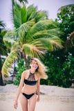 Jeune femme blonde attirante dans le bikini se tenant sur la plage sablonneuse le jour venteux Image stock