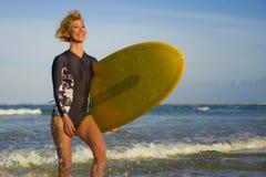 Jeune femme blonde attirante et heureuse de surfer en belle plage portant le panneau de ressac jaune marchant hors de la mer appr photographie stock