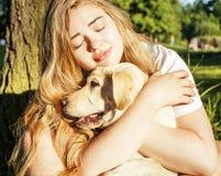 Jeune femme blonde attirante jouant avec son chien en parc vert à l'été, concept de personnes de mode de vie Image stock