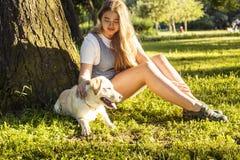 Jeune femme blonde attirante jouant avec son chien en parc vert à l'été, concept de personnes de mode de vie Photos libres de droits