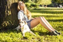 Jeune femme blonde attirante jouant avec son chien en parc vert à l'été, concept de personnes de mode de vie Photo stock