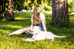 Jeune femme blonde attirante jouant avec son chien en parc vert Photo stock