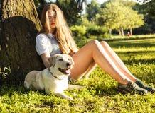 Jeune femme blonde attirante jouant avec son chien en parc vert Image libre de droits