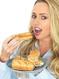 Jeune femme blonde attirante se tenant et mangeant Saugage Rolls Photographie stock libre de droits