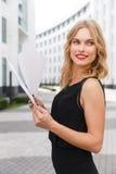 Jeune femme blonde aux cheveux frisés avec des documents photo libre de droits
