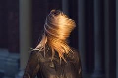 Jeune femme blonde avec des cheveux couvrant son visage images stock