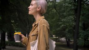 Jeune femme blonde avec du café potable de cheveux courts et aller du parc à sa voiture banque de vidéos