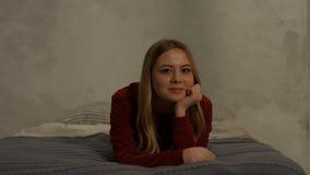 Jeune femme blonde avec du charme souriant sur le lit à la maison banque de vidéos