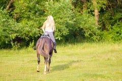 Jeune femme blonde avec le long cavalier de jockey de cheveux sautant sur un cheval de baie images stock