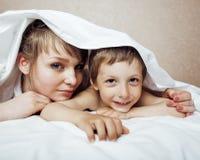 Jeune femme blonde avec le petit garçon dans le lit, la mère et le fils, famille heureuse Photographie stock libre de droits