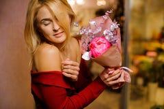 Jeune femme blonde avec les yeux fermés tenant un joli bouquet image stock