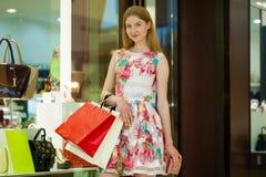 Jeune femme blonde avec quelques paniers dans le mail Photo libre de droits