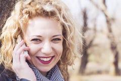 Jeune femme blonde bouclée parlant au téléphone dedans dehors images stock