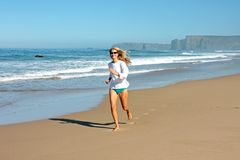 Jeune femme blonde courant à la plage Photographie stock libre de droits