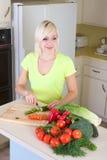 Jeune femme blonde découpant des légumes en tranches sur la cuisine Photo stock