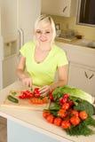 Jeune femme blonde découpant des légumes en tranches sur la cuisine Image stock