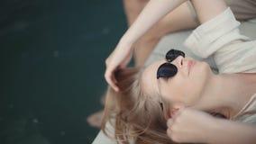 Jeune femme blonde détendant sur le pilier en bois un jour d'été banque de vidéos