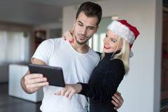 Jeune femme blonde dans le chapeau de Santa faisant des emplettes en ligne pour des WI de Noël Photographie stock