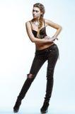 Jeune femme blonde dans le dessus noir et jeans posant sur le backgro léger Image libre de droits