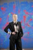 Jeune femme blonde dans un costume élégant contre le mur grunge Photos libres de droits