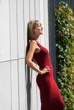 Jeune femme blonde dans une robe rouge se penchant contre le mur en bois Images stock