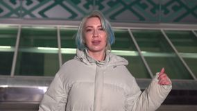 Jeune femme blonde, dans une veste blanche de mode descendant la rue centrale abandonnée la nuit banque de vidéos