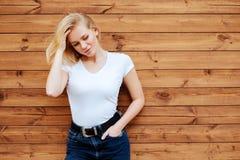 Jeune femme blonde de mode au-dessus de fond en bois photographie stock libre de droits