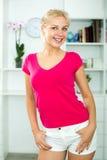 Jeune femme blonde de sourire à l'intérieur Photographie stock