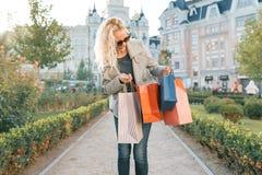 Jeune femme blonde de sourire avec les cheveux bouclés avec des sacs pour faire des emplettes, fond ensoleillé de ville, heure d' photos stock