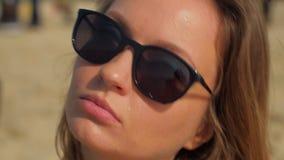 Jeune femme blonde de sourire avec les lunettes de soleil noires sur une plage dans le jour d'été ensoleillé banque de vidéos