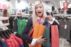 Jeune femme blonde de sourire dans le magasin d'habillement Photographie stock libre de droits
