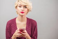 Jeune femme blonde de Stylysh appelle le service de mini-messages et employant l'isola de téléphone image stock