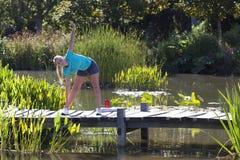 Jeune femme blonde en bonne santé étirant ses bras vers le bas au-dessus de l'eau photos libres de droits