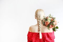 Jeune femme blonde en jeans de maman et bouquet sup?rieur de participation de chemise de culture des tulipes photo stock