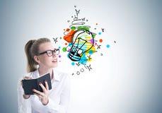 Jeune femme blonde en verres écrivant, bonne idée Images stock