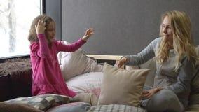 Jeune femme blonde et petite fille jouant sur le lit avec des oreillers banque de vidéos