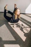 Jeune femme blonde faisant l'asana dans le studio de yoga Photos stock