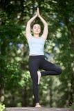 Jeune femme blonde faisant la pose de yoga d'arbre Photographie stock