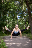 Jeune femme blonde faisant la posture de yoga de luciole photo stock