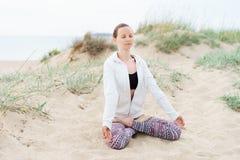 Jeune femme blonde faisant la pratique en matière de yoga de matin dehors sur le b photos libres de droits