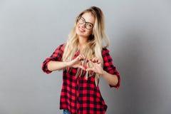 Jeune femme blonde gaie montrant le geste de coeur Photos libres de droits