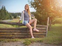 Jeune femme blonde heureuse à la mode posant dans le paysage rural photo libre de droits